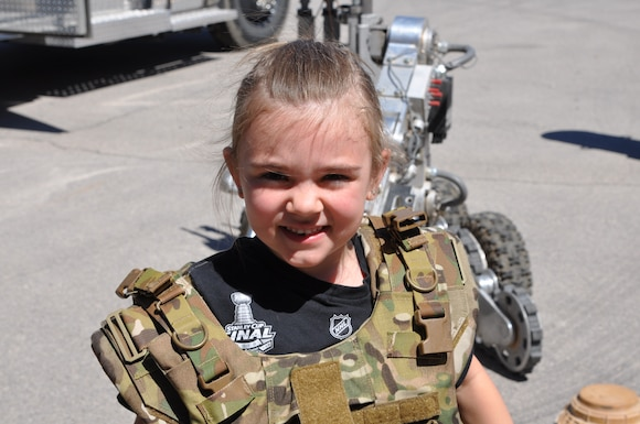 5-year-old Avery dons body armor during a tour of the 926th Wing's Explosive Ordnance Disposal unit April 27 at Nellis Air Force Base, Nev. Her mother, Air Force Staff Sgt. Sabrina Yeghiazarian, the 926th Wing's Development and Training Flight Chief, brought Avery to work on National Take Our Daughters and Sons to Work Day to see firsthand the capability the wing provides. (U.S. Air Force photo by Maj. Candice Allen)