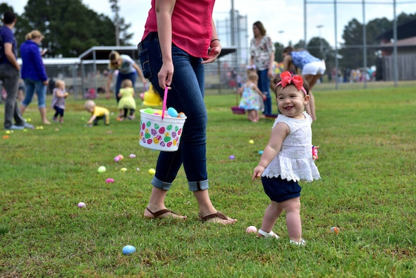 A young girl walks around a field full of Easter eggs.