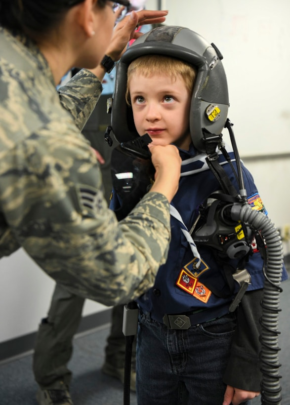 Senior Airman Maricely Fuentes, 104th Operations Support Flight technician, helps a Cub Scout put on a helmet during a base tour April 19, 2019, at Barnes National Guard Base, Mass.  Cub Scouts from Pack 338 and Troop 338 visited the 104th Fighter Wing and gained a better understanding of what the Air National Guard does on a daily basis. (U.S. Air National Guard photo by Airman 1st Class Randy Burlingame)