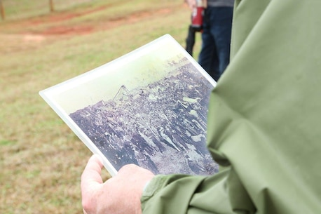 A Marine holds a photograph of prisoners of war at Camp Sumter, commonly known as the Andersonville Prison, during a recent tour.