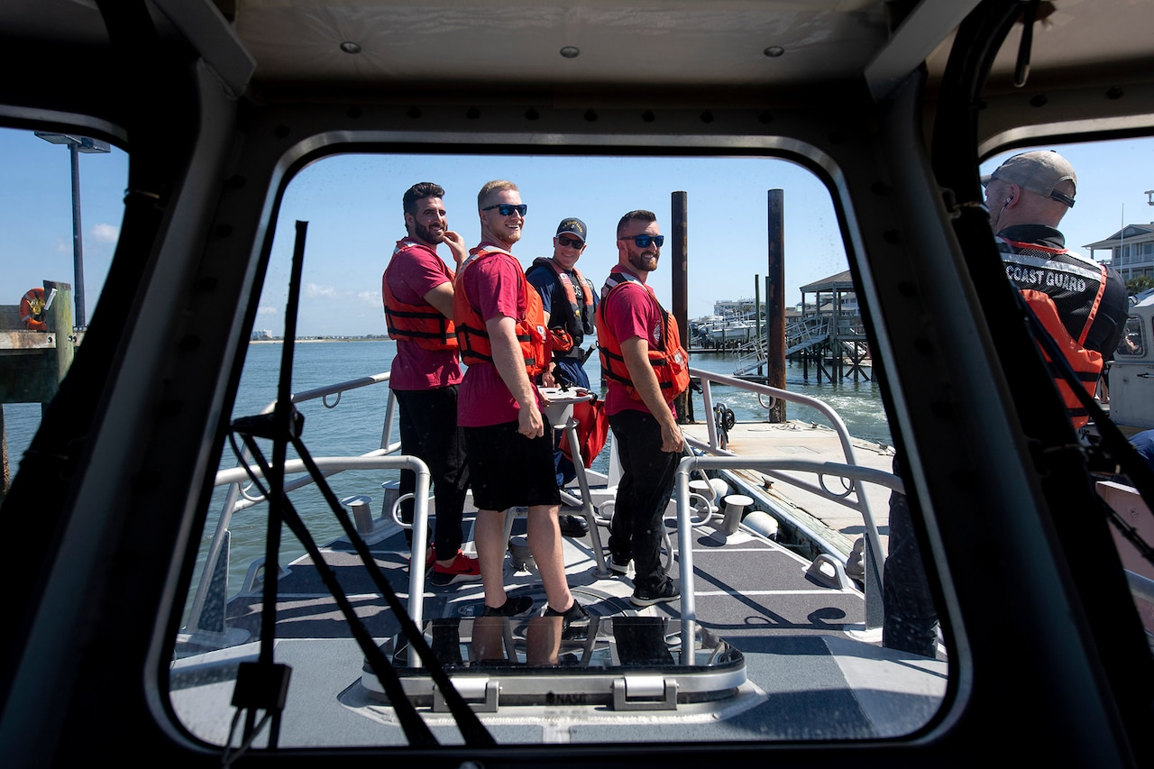 Four men look over their shoulders to listen to a Coast Guard member.