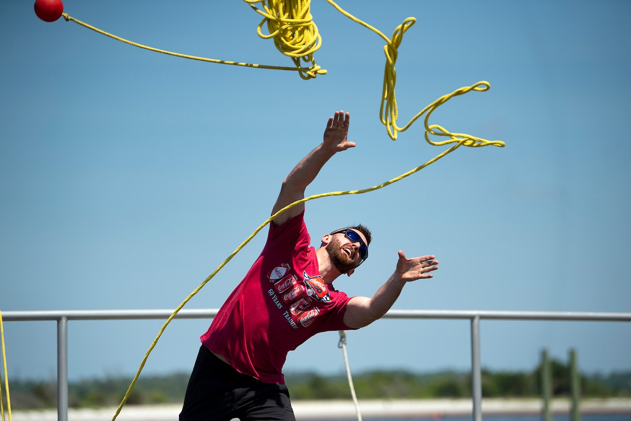 A man throws a yellow rope.