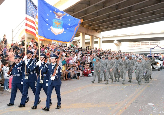 The 433rd Airlift Wing's Honor Guard leads the 433rd Airlift Wing and 960th Cyberspace Wing walkers and float on Broadway Street in downtown San Antonio during the 71st annual Fiesta Flambeau Parade April 27. More than 750,000 spectators lined the 2.6-mile-long route see more than 200 floats and marching bands perform in the grand finale of Fiesta Week.