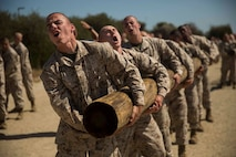 Recruits with Kilo Company, 3rd Recruit Training Battalion, perform side curls with a log at Marine Corps Recruit Depot San Diego, April 22.