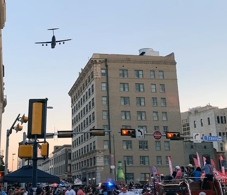 A 433rd Airlift Wing C-5M Super Galaxy flies over the Alamo at an altitude of 1,000 feet as the sun sets in downtown San Antonio as it approaches the Alamo during the 71st annual Fiesta Flambeau Parade April 27. The flyover marks the first time the parade has had a flyover by the largest aircraft in the United States military.