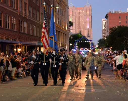 The 433rd Airlift Wing's Honor Guard leads the 433rd Airlift Wing and 960th Cyberspace Wing walkers and float on Commerce Street in downtown San Antonio during the 71st annual Fiesta Flambeau Parade April 27. More than 750,000 spectators lined the 2.6 mile-long route see more than 200 floats and marching bands perform in the grand finale of Fiesta Week.