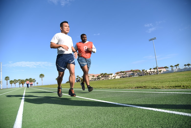 Lt. Col. Asan Bui runs alongside Senior Airman Kevin Frazier to cheer him on during a physical training test at Patrick Air Force Base, Florida, on Jan. 13, 2019. Both men are a part of the 920th Rescue Wing's Communications Flight, with Bui serving as the commander. Frazier expressed his gratitude and said the support helped him beat his previous record.  (U.S. Air Force photo by Senior Airman Brandon Kalloo Sanes)
