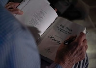 An Army Air Corps retiree signs a book.
