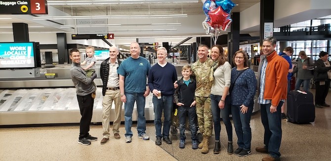 Col. Sean P. Pierce, 446th Airlift Wing commander, is welcomed home at the Seattle International Airport by family and 446th Reserve Citizen Airmen in March. Pierce served as the Mobility Forces director for U.S. Central Command, working for the CEPAC Air Forces Central Command (CFACC) commander in Qatar. (Courtesy Photo)
