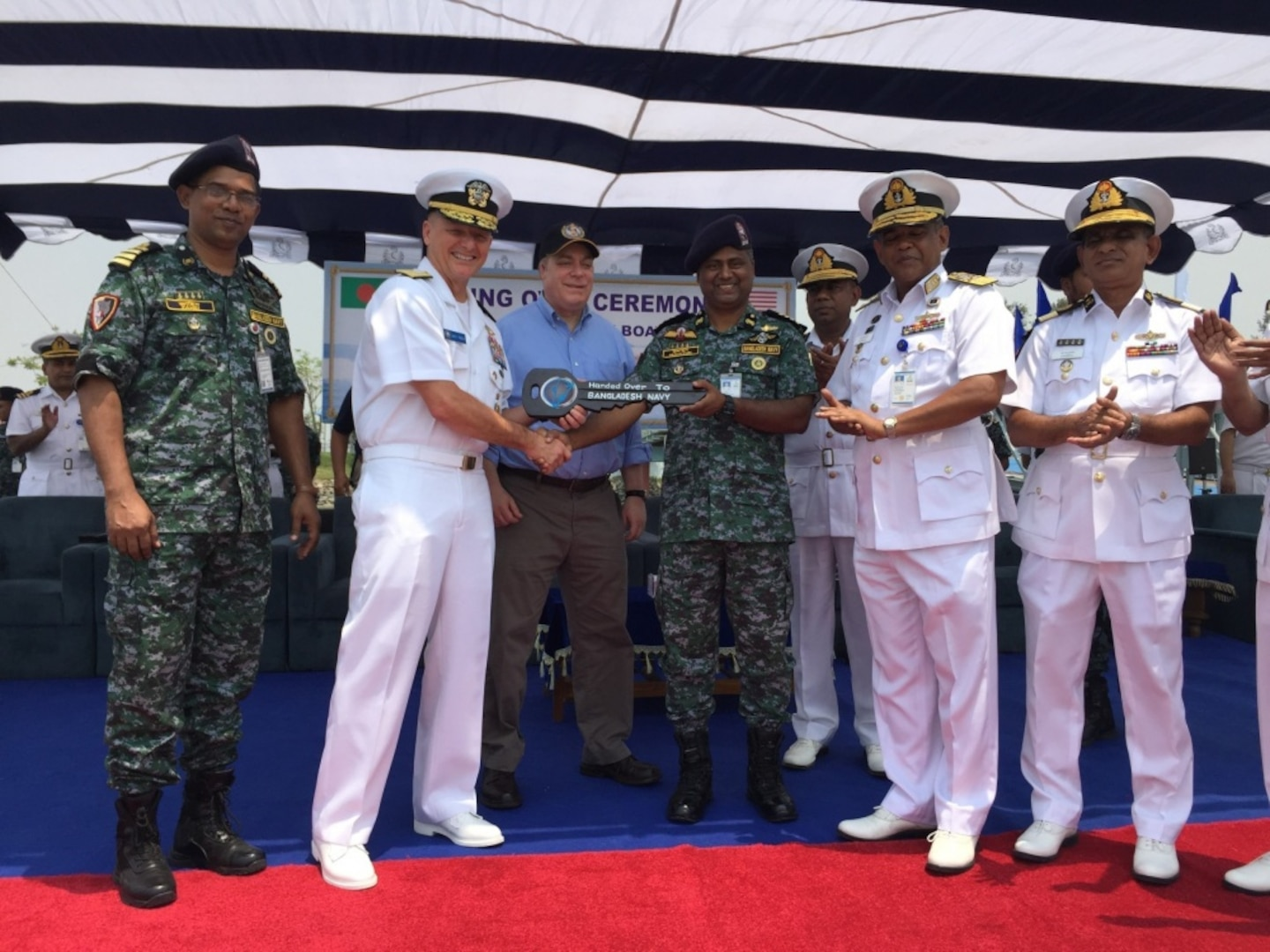 190425-N-ZZ999-001 CHITTAGONG, Bangladesh (April 25, 2019) Rear Admiral Joey Tynch, commander, Logistics Group Western Pacific, left, presents a symbolic key to Bangladesh Navy senior delagates during a ceremony at the Special Warfare Diving and Salvage (SWADS) Headquarters in Chittagong. Five metal patrol boats were handed over to the Bangladesh Navy and a ceremony was held commemorating the exchange of the crafts and celebrating the long-standing partnership between both nations. (Courtesy photo by Lt. Col. Matthew A. Kohler)