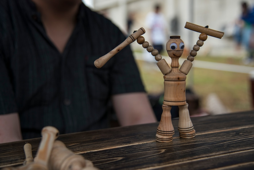 An action figure, 'Mokko Fighter,' stands on a table during the Tanabata Festival in Misawa City, Japan, July 26, 2019. The user controls the wooden figure's arms and legs to simulate a dancing or fighting performance for guest. This attraction compares to a modern-day puppet show. (U.S. Air Force photo by Branden Yamada)