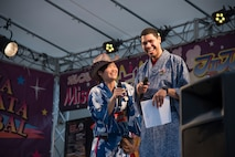 Shumi Kaufman, left, a 35th Force Support Squadron Airman and Family Readiness Center intercultural coordinator, and U.S. Air Force Staff Sgt. Tony Rodeback, an Armed Forces Network – Misawa producer, introduce contestants of the yukata fashion show during the Tanabata Festival in Misawa City, Japan, July 26, 2019. The fashion show featured a variety of guests wearing colorful and traditional Japanese summer kimonos. (U.S. Air Force photo by Branden Yamada)