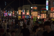 Attendees walk around during the Tanabata Festival in Misawa City, Japan, July 26, 2019. Event attendees enjoyed paper mache decorations, live musical performances, basketball games and a variety of food vendors in addition to socializing and connecting with each other. (U.S. Air Force photo by Branden Yamada)
