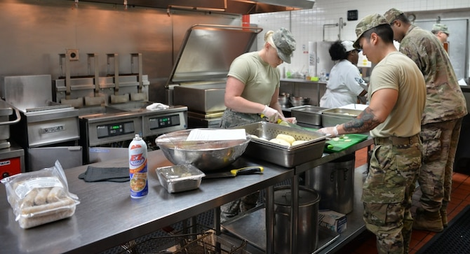 The food service team at the Crosswinds Dining Facility prepares lunch for service members at Nellis Air Force Base, Nevada, July 25, 2019. They work together to ensure new members are properly trained. Augmentees were sent to Nellis to help with the influx of customers during Red Flag and other exercises throughout the year. (U.S. Air Force photo by Tech. Sgt. Bryan Magee)