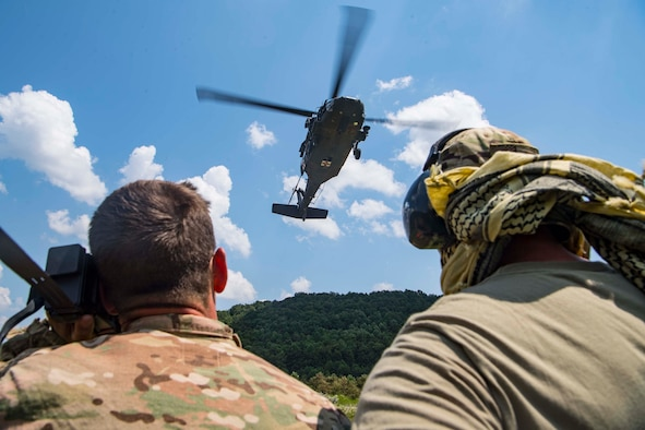 Two Airmen from the 130th Airlift Wing, McLaughlin Air National Guard Base, W.Va., look on as a U.S. Army UH-60 Blackhawk assigned to Company C., 2-104th General Support Aviation Battalion (MEDEVAC), Williamstown, W.Va., prepares to extract aircrew members from the field during combat survival training for Sentry Storm 19 held July 29, 2019, at the Hobet Mine site in Boone County, W.Va.