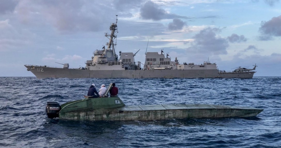 USS Michael Murphy's in the water next to a low profile vessel.