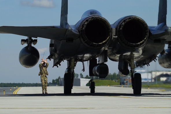 A U.S. Air Force Special Tactics Operator marshals an F-15 Strike Eagle to a forward arming and refueling point mission with USAFE aircraft during Operation Rapid Forge at Ämari Air Base, Estonia, July 18, 2019. Special Tactics is a U.S. Special Operation Command's tactical air and ground integration force, and the Air Force's special operations ground force, leading Global Access, Precision Strike, Personnel Recovery and Battlefield Surgery operations on the battlefield. The F-15E Strike Eagle is a dual-role fighter designed to perform air-to-air and air-to-ground missions, with the capability to fight at low altitude, day or night, and in all weather. Operation Rapid Forge involves NATO territories in order to enhance readiness and improve interoperability between U.S. allies and partners in Europe. (U.S. Air Force photo by Staff Sgt. Rose Gudex)