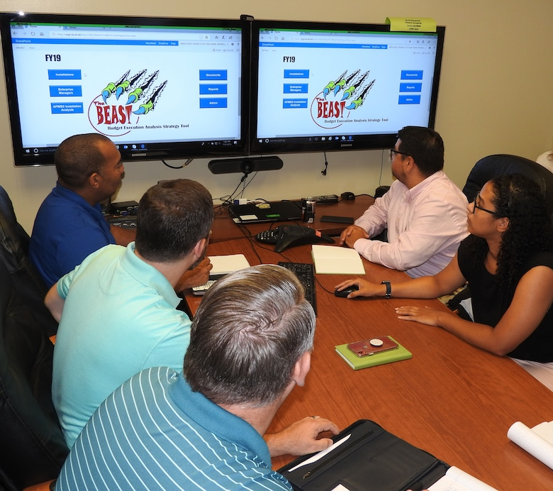 Members of AFIMSC's Budget Office Installation Support Team review the Budget Execution Analysis Strategy Tool (BEAST), to monitor the status of must pay and unfunded requirements at installations across the Air Force. (U.S. Air Force photo by Ed Shannon)