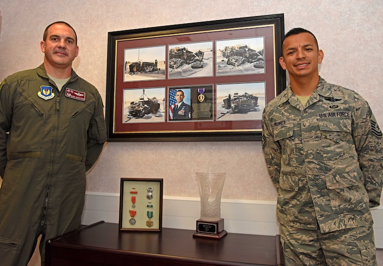 Colonel Robert Shelton, 100th Operations Group commander, left, and Chief Master Sgt. Cesar Flores, 100th OG superintendent, pose for a photo with Flores' Purple Heart plaque at RAF Mildenhall, England, July 24, 2019. Flores was awarded the Purple Heart and a wounded warrior designation after an armored vehicle he was in was struck by an improvised explosive device while deployed in Iraq in 2007. (U.S. Air Force photo by Airman 1st Class Brandon Esau)