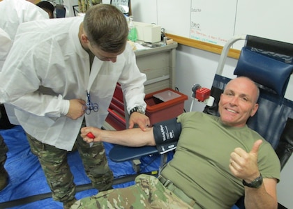 Army Spc. Joshua Gerstenberger, Fort Leonard Wood Blood Donor Center lab tech, prepares Army Maj. Gen. Frank Muth, Army Recruiting Command commanding general, to donate blood July 19. During the five-hour drive, 44 headquarters people donated to the Armed Services Blood Program. (Photo by Carl Norman).