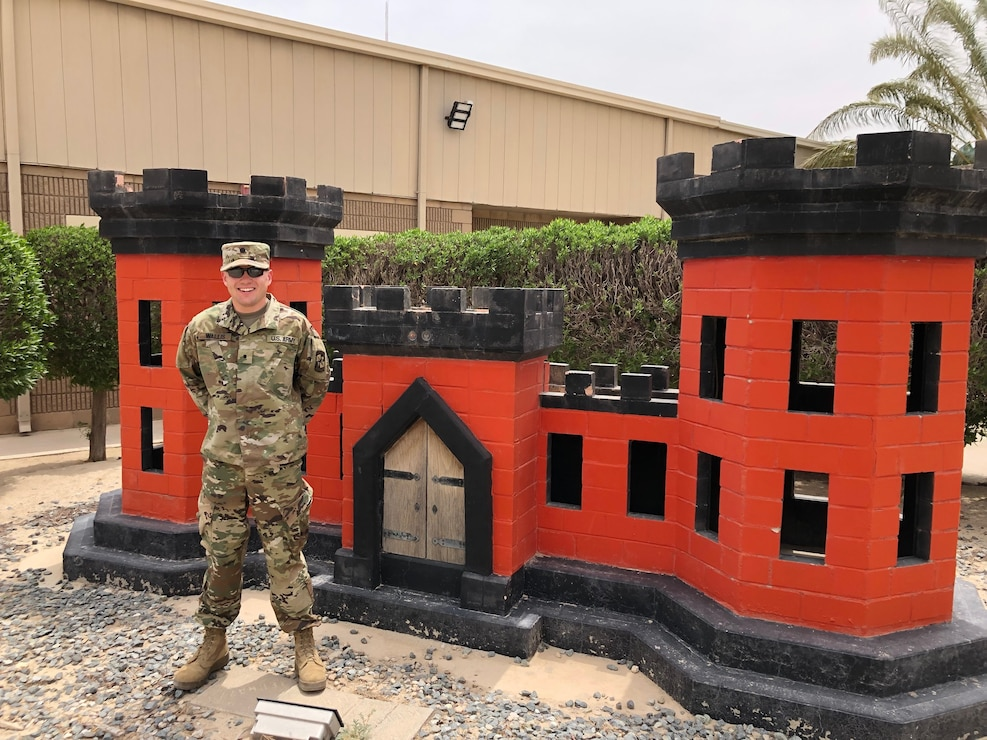 ROTC cadet in military uniform standing in front of a red castle, a symbol of the U.S. Army Corps of Engineers.