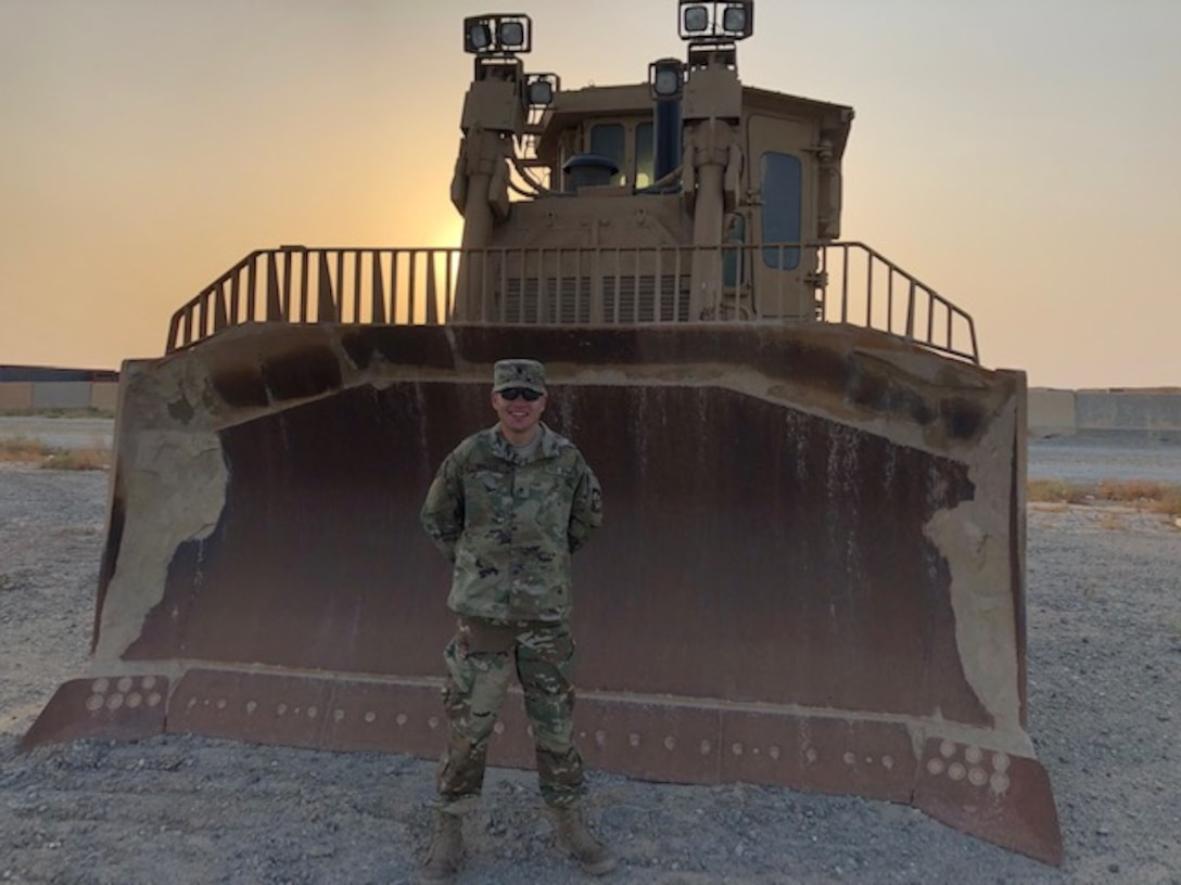 Man in military uniform standing in front of a large bull dozer in the desert.
