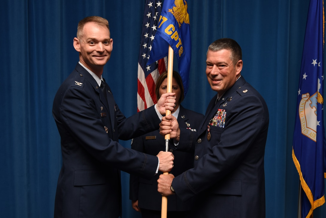 U.S. Air Force Lt. Col. William Beauter (right), outgoing 377th Comptroller Squadron commander, passes the guidon to Col. David Miller, 377th Air Base Wing commander, during a change of command ceremony at Kirtland Air Force Base, N.M., July 31, 2019. Beauter is scheduled to assume command of Reserve Officer Training Corps Det. 510. (U.S. Air Force photo by Senior Airman Eli Chevalier)