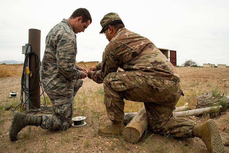 Air Force ROTC cadet Luke Carey, left, assisted by Staff Sgt. Guadalupe Corona, 775th Explosive Ordnance Disposal Flight, prepares to detonate an explosive charge at Hill Air Force Base, Utah, July 31, 2019. Over 80 cadets visited Hill as part of a professional development training program called Operation Air Force. The program gives cadets a greater understanding of the Air Force while introducing them to a variety of careers fields. (U.S. Air Force photo by R. Nial Bradshaw)