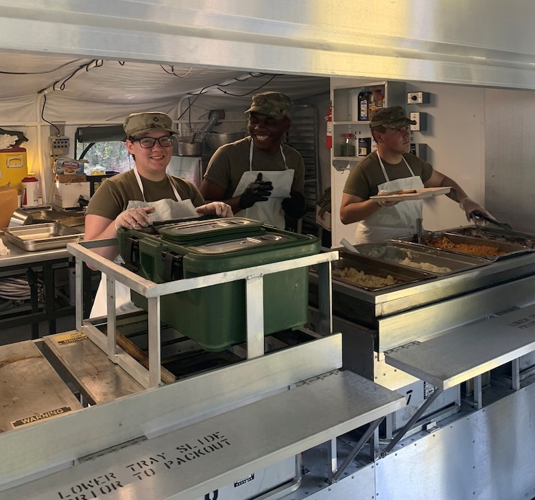Pfc Victoria Clark, Spec Sorin Tatah, and Pfc Delmar Osorio-Ortiz, assigned to the 642nd Aviation Support Battalion, New York Army National Guard, cook inside the Containerized on July 27th for their annual training at Fort Indiantown Gap, PA as part of the Connelly competition evaluation.