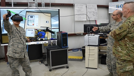 Command Sgt. Major John Wayne Troxell, senior enlisted advisor to the Chairman of the Joint Chiefs of Staff and the senior non-commissioned officer in the U.S. Armed Forces, observes as Staff Sgt. Jemima Alvarez, an instructor in the Biomedical Equipment Technician program, demonstrates a virtual interactive classroom modality that the program is testing as a training tool for repairing Expeditionary Deployable Oxygen Concentration System units while BMET instructor Master Sgt. Christian Bond explains how it works.