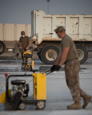 Two 380th Expeditionary Civil Engineer Squadron water and fuels technicians cut concrete during a rapid airfield damage repair exercise July 26, 2019, at Al Dhafra Air Base, United Arab Emirates. By cutting the concrete it can be broken up and removed to be filled with fast-curing concrete. (U.S. Air Force photo by Staff Sgt. Chris Thornbury)