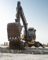 Senior Airman David Smith, 380th Expeditionary Civil Engineer Squadron heavy machine operator, operates an excavator to collect and lift concrete during a rapid airfield damage repair exercise July 26, 2019, at Al Dhafra Air Base, United Arab Emirates. Removing the concrete allows the team to replace the damaged area with new fast-curing concrete to get the airfield operational within hours. (U.S. Air Force photo by Staff Sgt. Chris Thornbury)