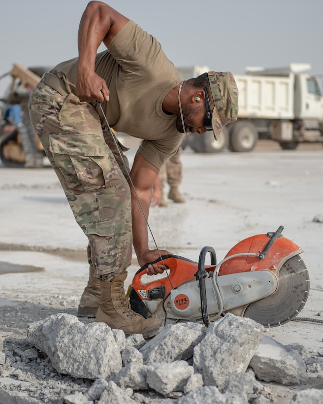 Senior Airman Brandon McLendon, 380th Expeditionary Civil Engineer Squadron heavy machine operator, pull starts a cut-off machine during a rapid airfield damage repair exercise July 26, 2019, at Al Dhafra Air Base, United Arab Emirates. The saw is used to cut rebar to create more room for an excavator to remove damaged concrete. (U.S. Air Force photo by Staff Sgt. Chris Thornbury)