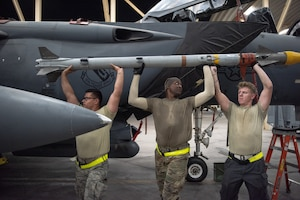 An F-15E Strike Eagle weapons load crew team lifts an AIM-9X Sidewinder missile to attach to a pylon July 15, 2019, at Al Dhafra Air Base, United Arab Emirates. The AIM-9X is an advanced infrared missile and the newest of the Sidewinder family of short-range air-to-air missiles carried on a wide range of fighter jets. (U.S. Air Force photo by Staff Sgt. Chris Thornbury)