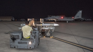 An F-15E Strike Eagle weapons load crew team prepares to lift an AIM-120D to attach to a pylon July 15, 2019, at Al Dhafra Air Base, United Arab Emirates. The AIM-120D is the latest Advanced Medium-Range Air-to-Air missile (AMRAAM) and features improved navigation, kinematics, lethality and hardware and software updates to enhance its electronic protection capabilities against more capable threats. (U.S. Air Force photo by Staff Sgt. Chris Thornbury)