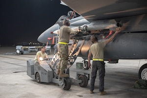 An F-15E Strike Eagle weapons load crew team attaches an AIM-120D to a pylon July 15, 2019, at Al Dhafra Air Base, United Arab Emirates. The AIM-120D is the latest Advanced Medium-Range Air-to-Air missile (AMRAAM) and features improved navigation, kinematics, lethality and hardware and software updates to enhance its electronic protection capabilities against more capable threats. (U.S. Air Force photo by Staff Sgt. Chris Thornbury)