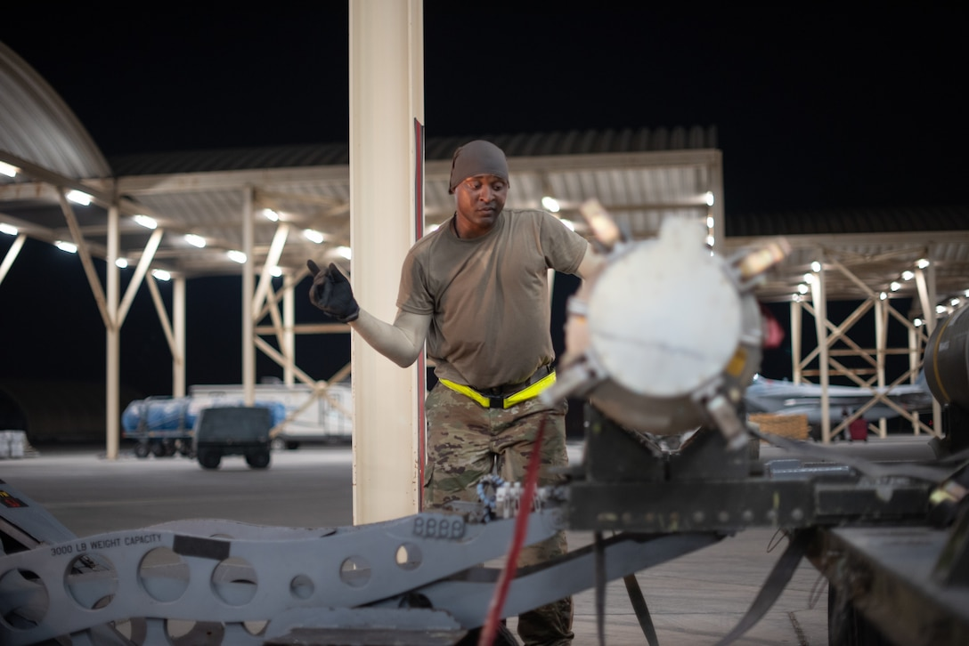 Staff Sgt. Kiefer May, 380th Expeditionary Aircraft Maintenance Squadron weapons load crew team chief, guides the lift operator July 15, 2019, at Al Dhafra Air Base, United Arab Emirates. Weapons load crews work 24/7 operations to support loading and configuring various munitions for the F-35A Lightning II, F-15E Strike Eagle and F-15C Eagle jets at ADAB. (U.S. Air Force photo by Staff Sgt. Chris Thornbury)