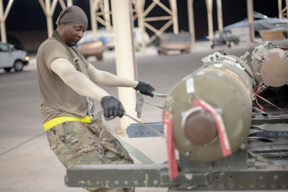 Staff Sgt. Kiefer May, 380th Expeditionary Aircraft Maintenance Squadron weapons load crew team chief, pulls a munition away from a trailer July 15, 2019, at Al Dhafra Air Base, United Arab Emirates. Weapons load crews work 24/7 operations to support loading and configuring various munitions for the F-35A Lightning II, F-15E Strike Eagle and F-15C Eagle jets at ADAB. (U.S. Air Force photo by Staff Sgt. Chris Thornbury)
