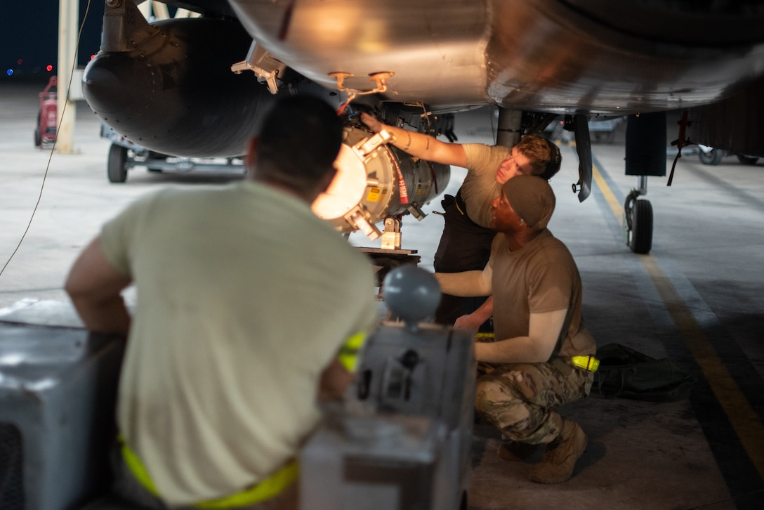 An F-15E Strike Eagle weapons load crew team attaches a munition to a pylon July 15, 2019, at Al Dhafra Air Base, United Arab Emirates. Diverse weapons loads on the F-15E arm the jet with a multitude of capabilities while flying in support of maritime combat air patrol missions in the Arabian Gulf. (U.S. Air Force photo by Staff Sgt. Chris Thornbury)