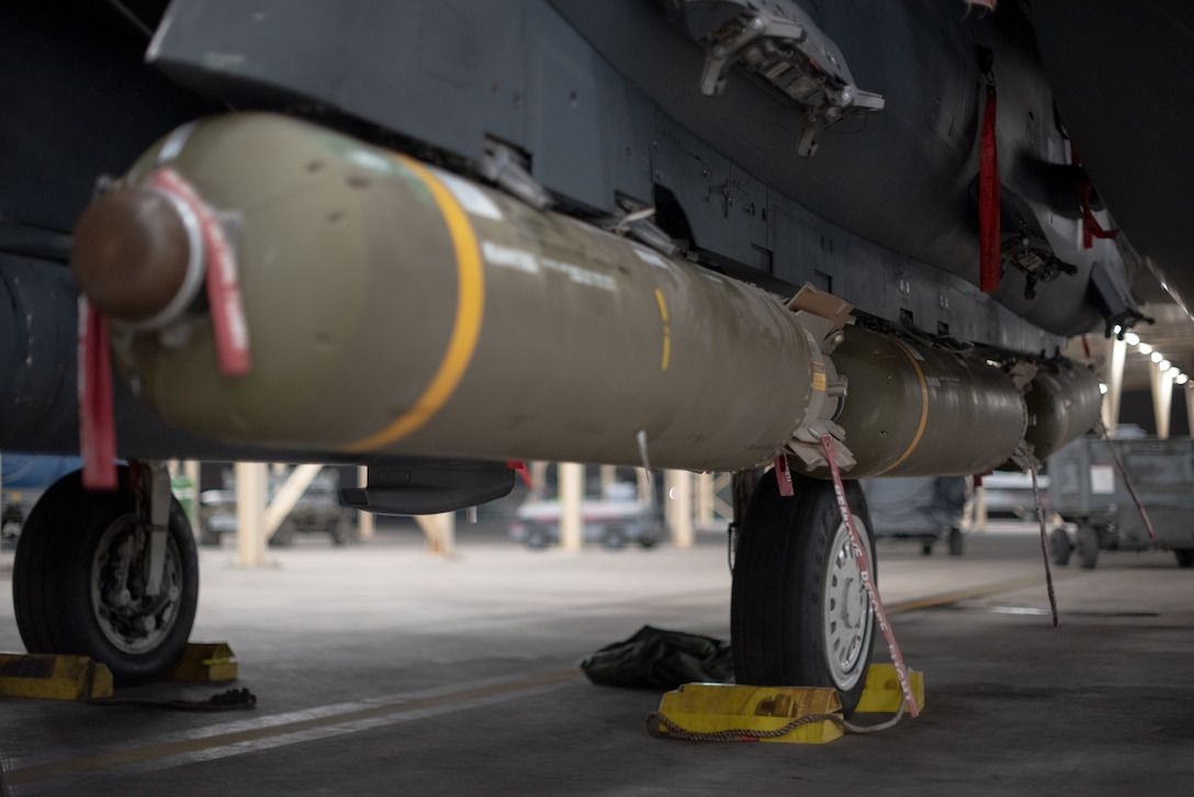 Munitions sit below an F-15E Strike Eagle July 15, 2019, at Al Dhafra Air Base, United Arab Emirates. Diverse weapons loads on the F-15E arm the jet with a multitude of capabilities while flying in support of maritime combat air patrol missions in the Arabian Gulf. (U.S. Air Force photo by Staff Sgt. Chris Thornbury)