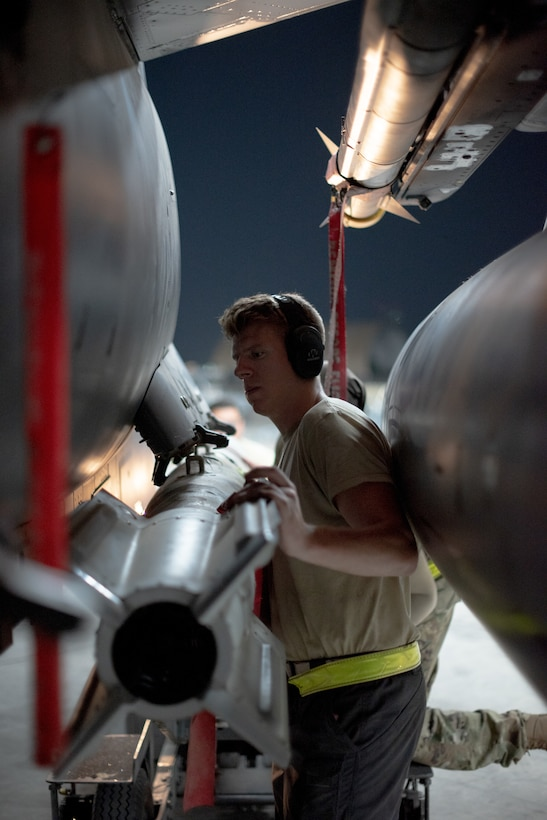 Senior Airman Sean Logan, 380th Expeditionary Aircraft Maintenance Squadron weapons load crew team member, helps attach a GBU-12 to an F-15E Strike Eagle July 15, 2019, at Al Dhafra Air Base, United Arab Emirates. The F-15E is a dual-role fighter designed to perform air-to-air and air-to-ground missions and currently supporting surface combat air patrol operations in the Arabian Gulf. (U.S. Air Force photo by Staff Sgt. Chris Thornbury)