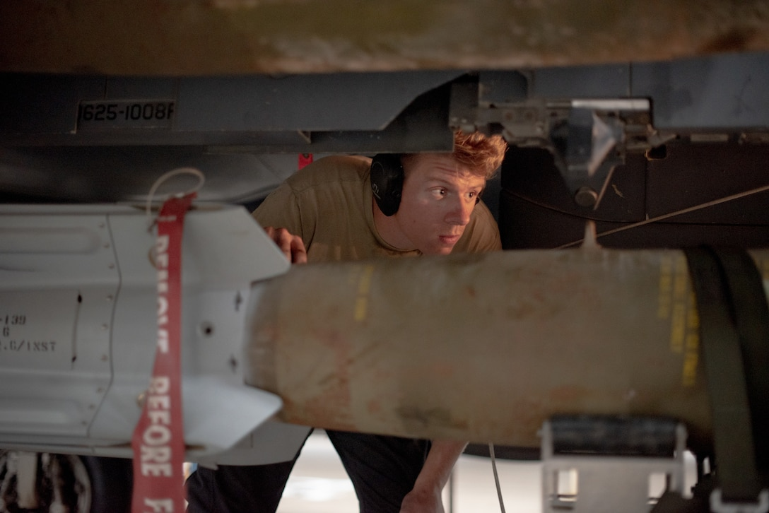 Senior Airman Sean Logan, 380th Expeditionary Aircraft Maintenance Squadron weapons load crew team member, watches a lift driver move a munition under an F-15E Strike Eagle July 15, 2019, at Al Dhafra Air Base, United Arab Emirates. The F-15E has the capability to carry any air-to-surface weapon in the Air Force inventory. (U.S. Air Force photo by Staff Sgt. Chris Thornbury)