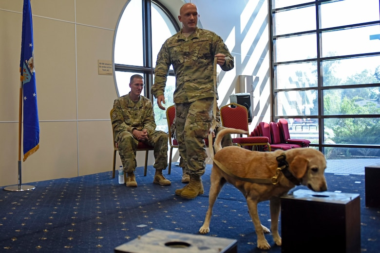 "U.S. Air Force Staff Sgt. Nicholas Fletcher, 39th Security Forces Squadron military working dog trainer, conducts a ""final sniff"" with Autumn, his MWD, during the latter's retirement ceremony at Incirlik Air Base, Turkey, July 29, 2019. The final sniff is an activity for a retiring working dog in which it detects a hidden object for the last time. (U.S. Air Force photo by Staff Sgt. Joshua Magbanua)"