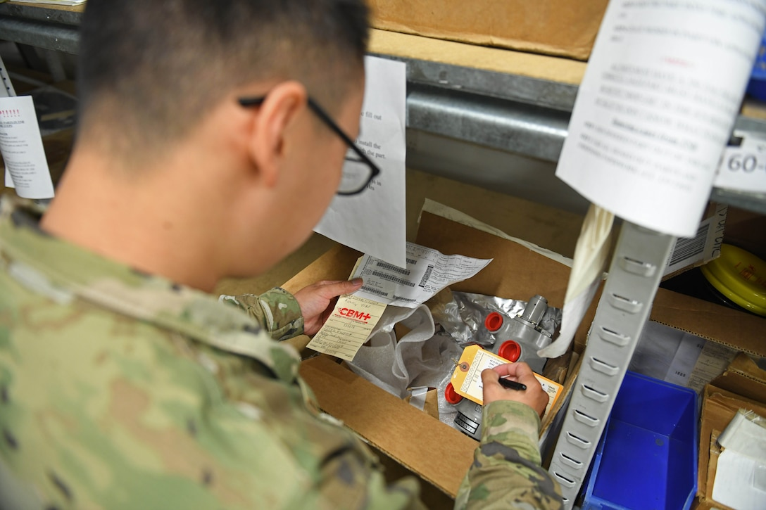 Senior Airman Grant Vang, 100th Logistics Readiness Squadron decentralized maintenance support journeyman, fills out a label for maintenance supplies at RAF Mildenhall, England, July 31, 2019. The 100th DMS supports five different squadrons on RAF Mildenhall encompassing three different major commands. (U.S. Air Force photo by Senior Airman Luke Milano)