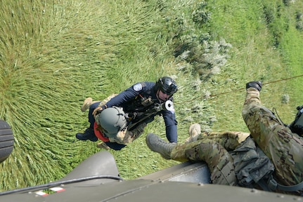 Chief Chris Baker, South Bend Fire Department and Sgt. Samantha Baker are hoisted in to a UH-60 Balck Hawk by Sgt. Todd D. Overbeck at Kingsbury, Indiana July 23. All are members of the Indiana HART, a joint miliatary-civilian serach and rescue operation teaming Indiana Army National Guard aviation with South Bend Fire Department rescuers.