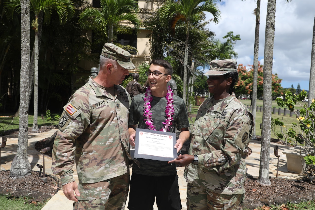 A teen accepts a certificate from two Army leaders. A statue and several palm trees are in the background.
