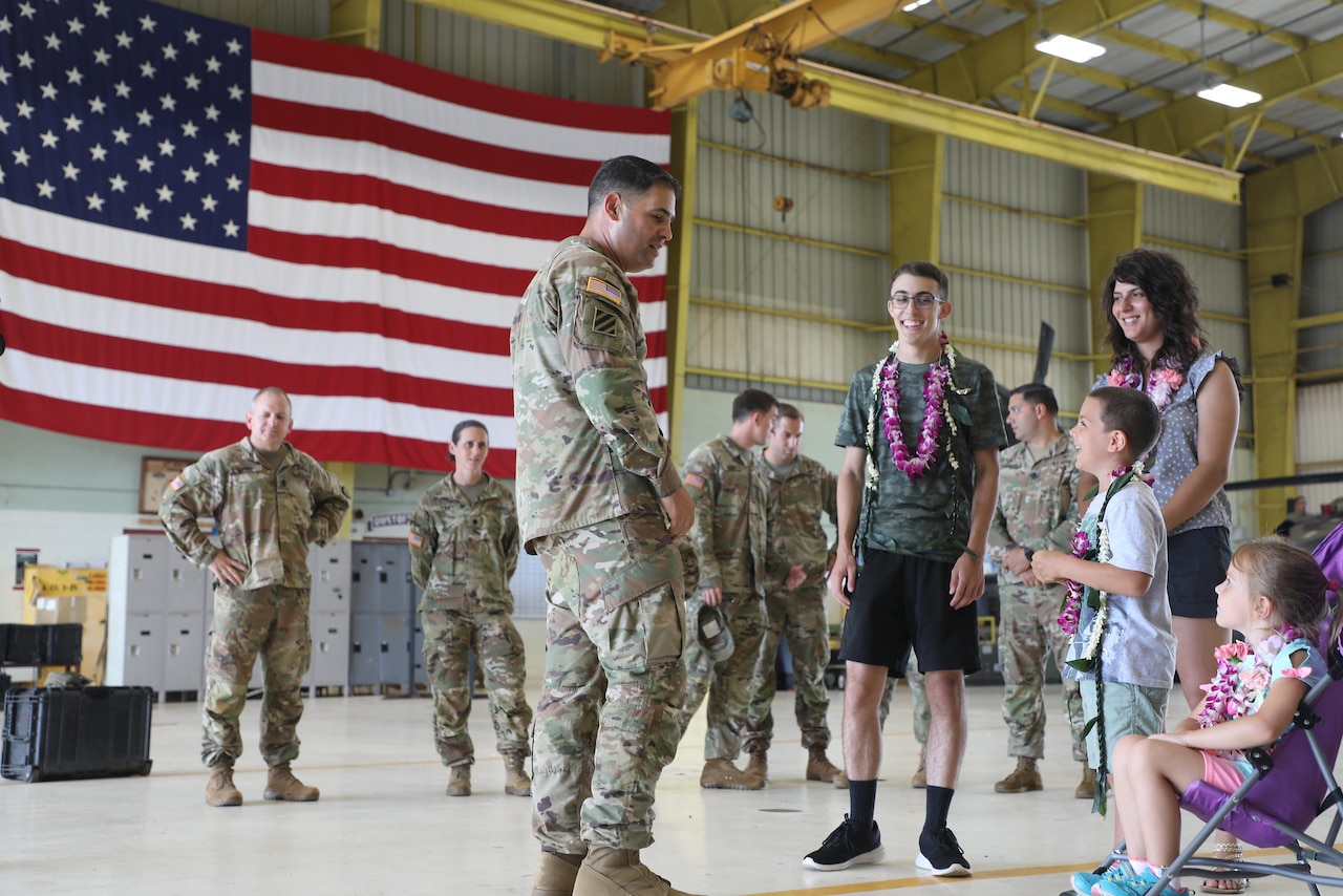 An Army colonel talks with a family in an aircraft hangar that has a large American flag draped in the background.