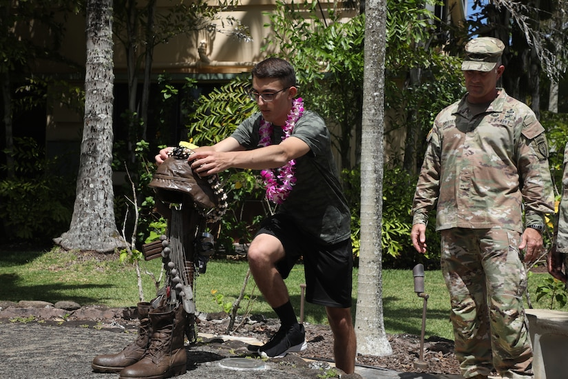 A teen places a Hawaiian lei on a memorial statue depicting a fallen soldier while a soldier watches.
