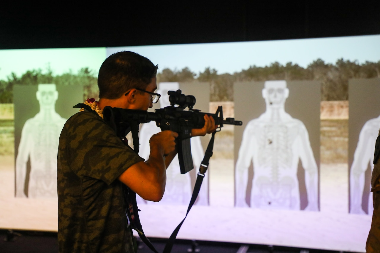 A teen points a rifle at a simulated gun range target.