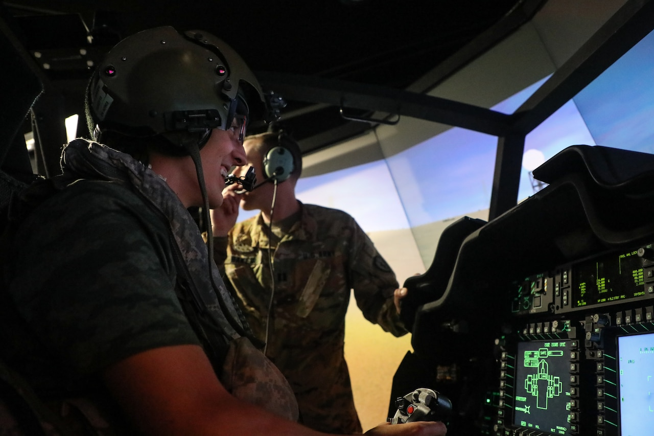 A teen sits in the pilot seat of a helicopter simulator.